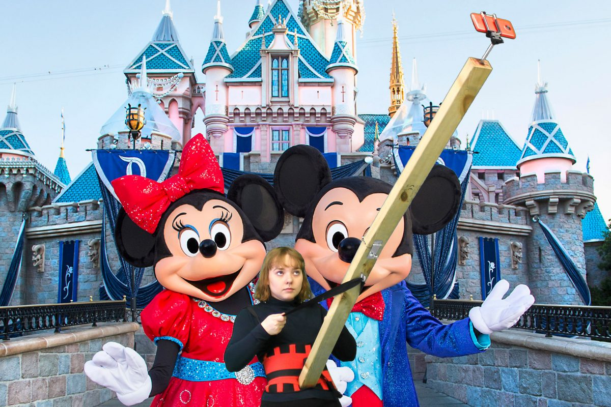 Artist with giant wooden selfie stick, at Disneyland