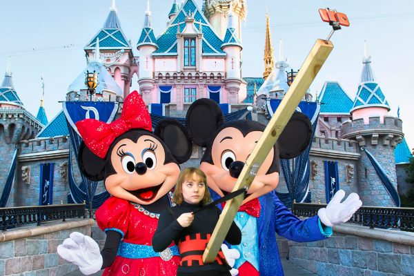 Performer with giant wooden selfie stick, at Disneyland
